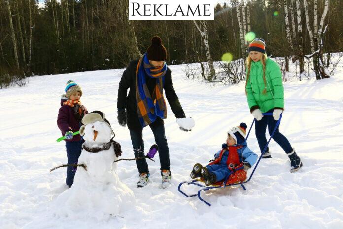 Mor, far og børn leger i sneen
