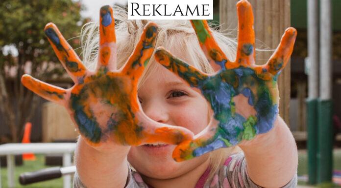 Lille pige med maling på håndfladerne
